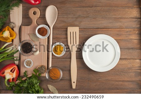 Various spices and vegetables on wooden table - stock photo