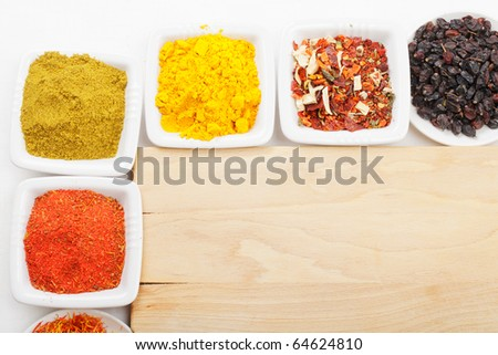 Various spices at empty wooden board above view