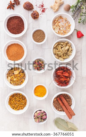 Various spices, dried and fresh herbs on table. An arrangement of  spices and herbs over rustic background.  Top view, vintage toned image. Natural light
