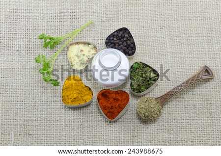 Various spices in heart shaped containers with salt in the middle on a tablecloth - stock photo