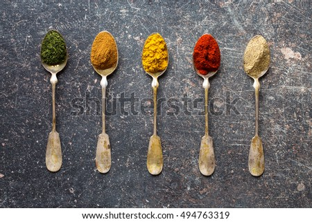 Various spices in spoons on old kitchen table. Top view.