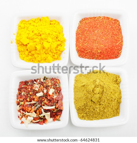 Various spices in white dishes on tablecloth above view