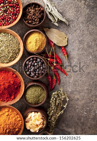 Various spices in wooden bowls on stone surface - stock photo