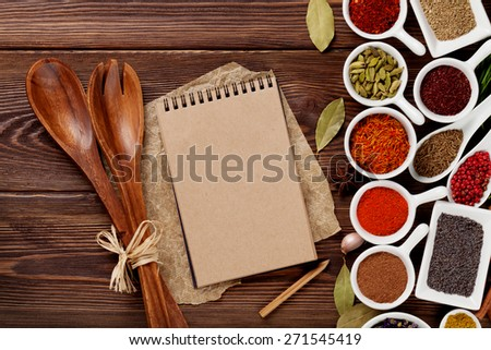 Various spices on wooden background. Top view with notepad for copy space   - stock photo