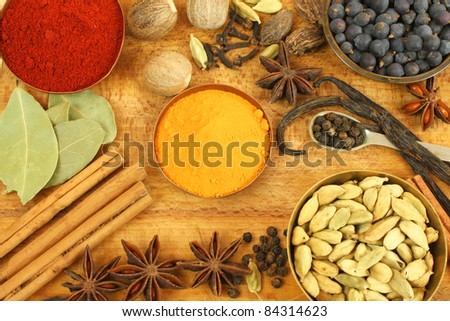 Various spices on wooden board - vintage style background - stock photo