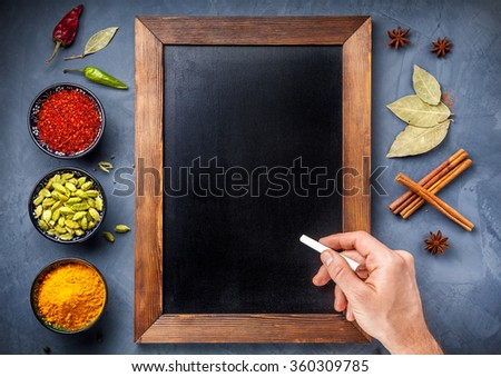 Various Spices powder turmeric, cardamom, chili, paprika, ginger, star anise and clove near blackboard  and hand with white chalk on grunge background. Free space for your text