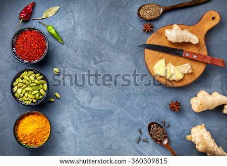 Various Spices powder turmeric, chili, bayberry, bay leaf, ginger on cutting board, cinnamon, cumin, star anise on grey stone background with space for your text, shot from top view close-up - stock photo