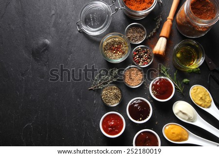 Various Spicy Ingredients for Recipe on Black slate Table with Copy Space on Left Side. - stock photo