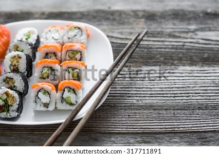various sushi on white plate with chopsticks on wooden background - stock photo