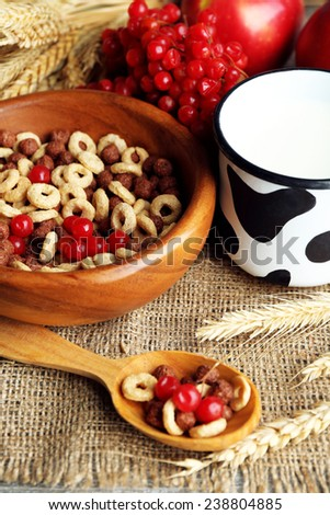 Various sweet cereals in bowl, fruits and mug with milk on napkin, on color wooden background - stock photo