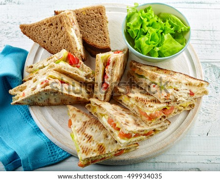 various triangle sandwiches on wooden cutting board
