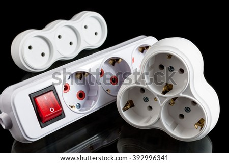 Various triple electrical plug outlet on black background - stock photo