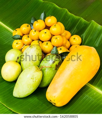 Various tropical fruit on banana leaf . - stock photo