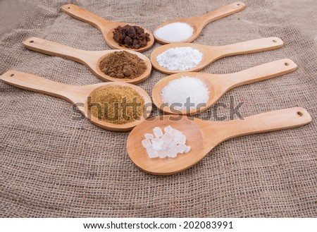 Various type of sugar on wooden spoon over gunny sack background - stock photo