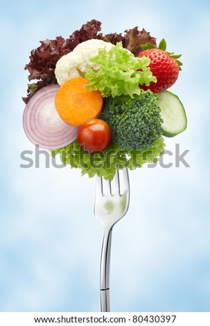 various type of vegetables on fork against blue background - stock photo