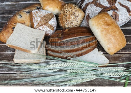 Various types of bread with cereal ears on a wooden table.