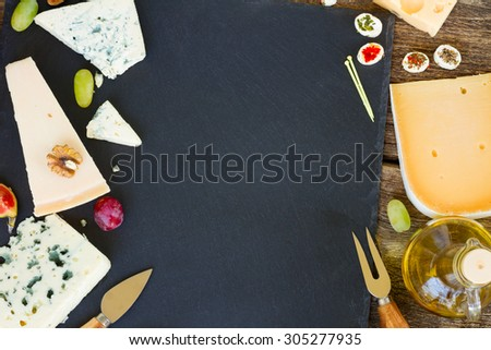 various types of cheese and appetizer on black cutting board with copy space, top view - stock photo