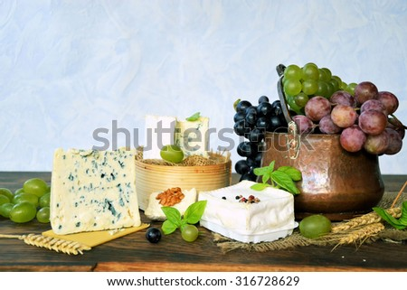 various types of cheese and grapes on a wooden background, natural food - stock photo