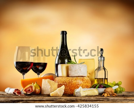 Various types of cheese, glasses and bottle of red wine placed on wooden table, copyspace for text. Abstract brown blur background - stock photo