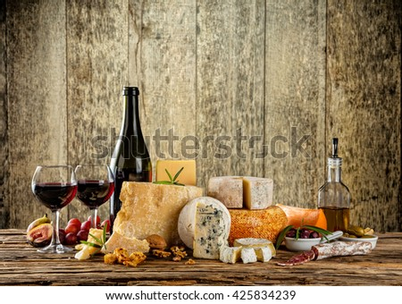Various types of cheese, glasses and bottle of red wine placed on wooden table, copyspace for text. Wooden planks on background - stock photo