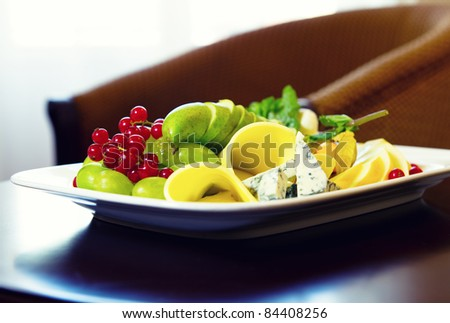 Various types of cheese, grapes and redcurrant closeup composition - stock photo