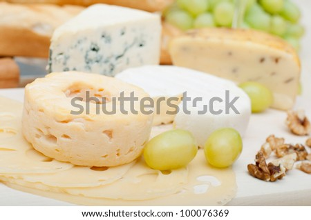 Various Types of Cheese, Grapes and Walnuts on Wooden Chopping Board - stock photo