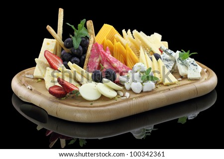 Various types of cheese on a cheese platter - stock photo