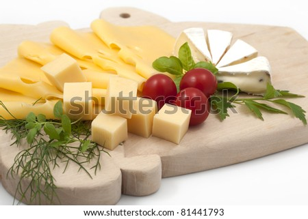 Various types of cheese on a wooden board - stock photo