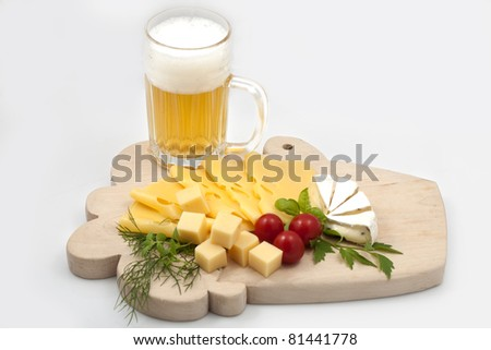 Various types of cheese on a wooden board with beer - stock photo