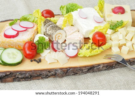 Various types of cheese on a wooden plate. - stock photo