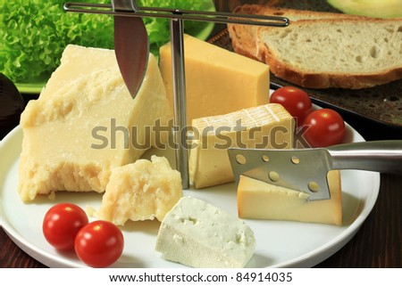 Various types of cheese on ceramic platter.