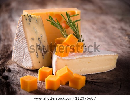 Various types of cheese on wood - stock photo