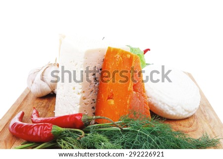 various types of cheese on wooden board with hot peppers and dill isolated over white background - stock photo