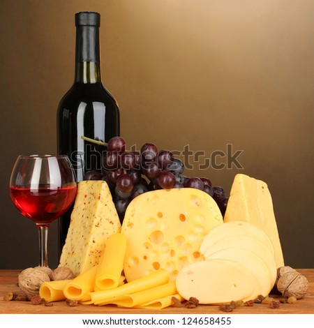 Various types of cheese on wooden table on brown background - stock photo