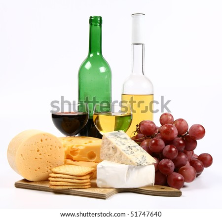 Various types of cheese (swiss, yellow, brie, blue cheese) with red and white wine, red grapes and crackers on white background - stock photo