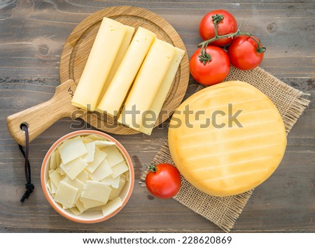 Various types of cheese, tomatoes on wooden background - stock photo