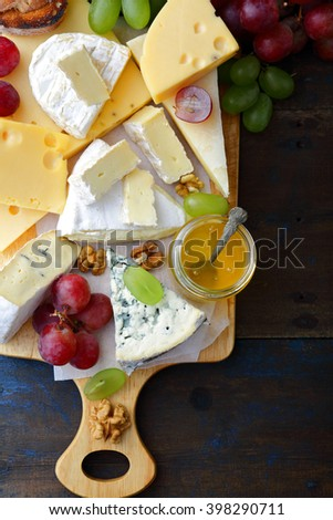 Various types of cheese with honey, grapes, bread and walnuts on cutting board on old wooden table. Top view - stock photo