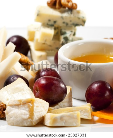 Various Types of Cheese with Honey Sauce and Grapes