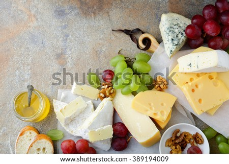 Various types of Cheeses with grapes, honey, bread and walnuts on slate background