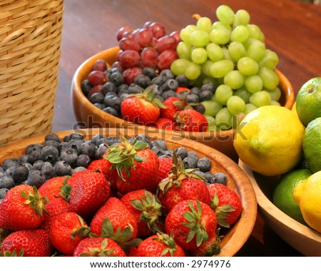 Various Types of Fruit Arranged and Displayed in Wooden Bowls and Baskets. - stock photo