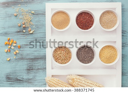 Various types of grains in bowls ( quinoa,amaranth, millet, chia,buckwheat ) with  rice, chickpea and corn next to bowls  on rustic blue  table. Top view, vintage toned image, blank space   - stock photo