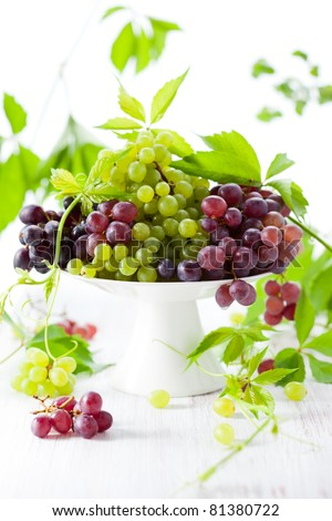 Various types of grapes with leaves on a cake stand - stock photo