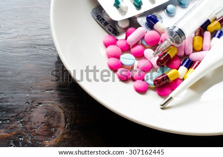 Various types of medicines, syringes and thermometers. In white dish concept of some people who need medicines instead of eating.
