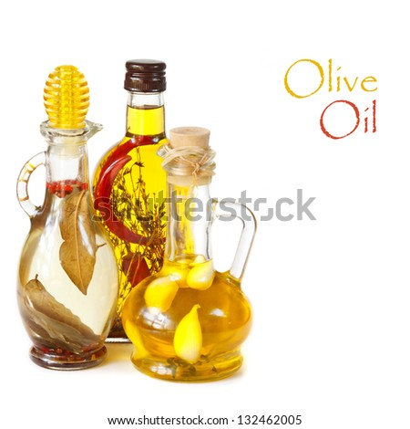 Various types of olive oil with spices on a white background. - stock photo