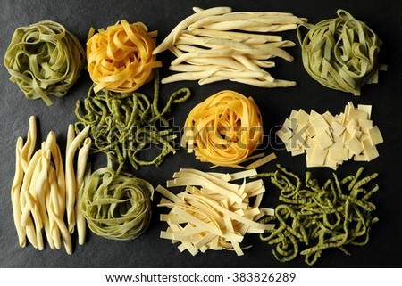 Various types of pasta on a black ceramic background. - stock photo