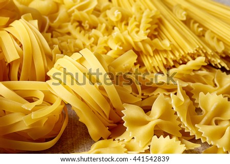 Various types of pasta on grey stone table