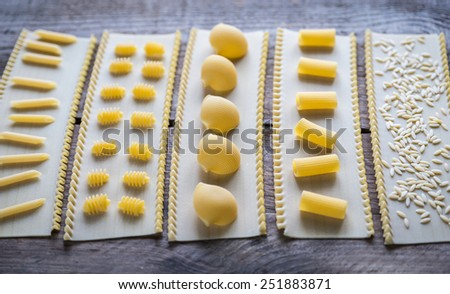 Various types of pasta on lasagne sheets - stock photo