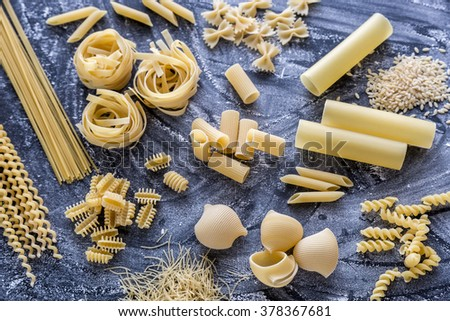 Various types of pasta on the dark flour dusted background - stock photo