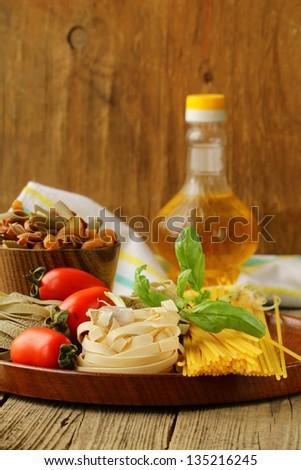 Various types of pasta (spaghetti, fettuccini, penne) and tomato - stock photo
