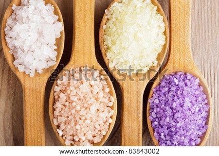 Various types of spa sea salt in wooden spoons closeup - stock photo